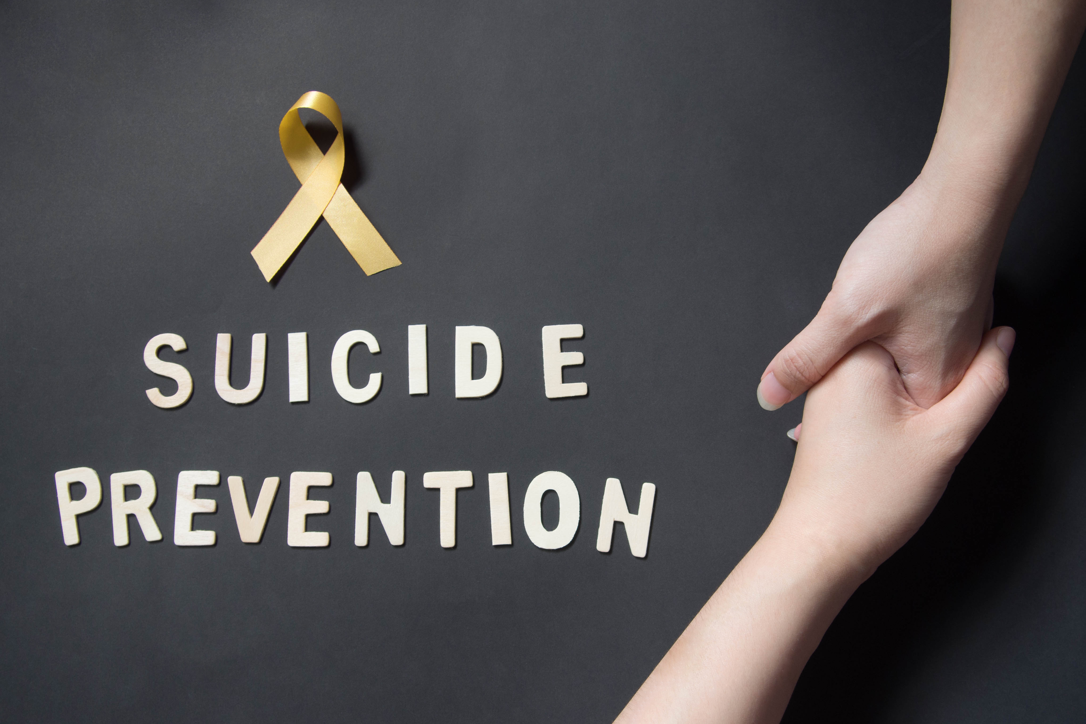 Two hands with suicide prevention written beside them and a yellow ribbon