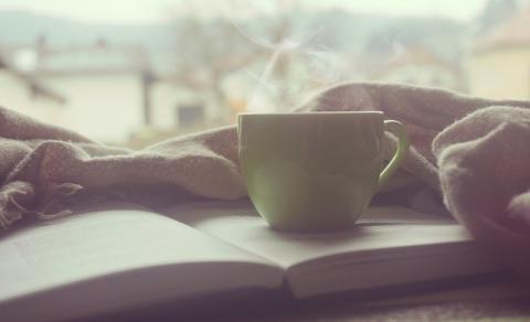 Coffee mug on open book