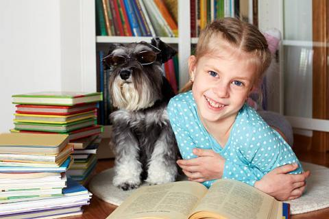 Little girl with dog and books